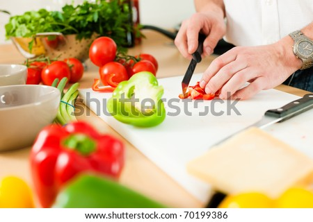 Man in the kitchen � only hands to be seen � is preparing the vegetables for dinner or lunch