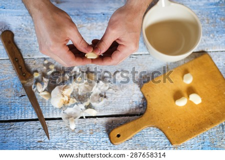 Man in the kitchen peeling garlic cloves for a dressing