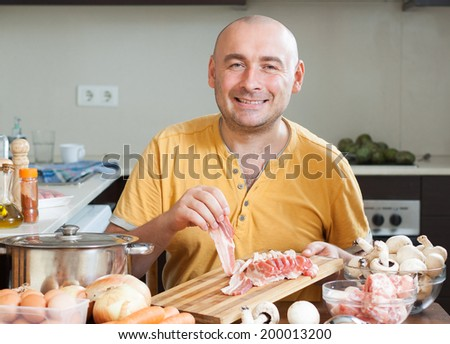 Man in the kitchen  preparing meat   - stock photo