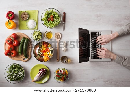 Man in the kitchen searching for recipes on his laptop with food ingredients and fresh vegetables on the left, top view - stock photo