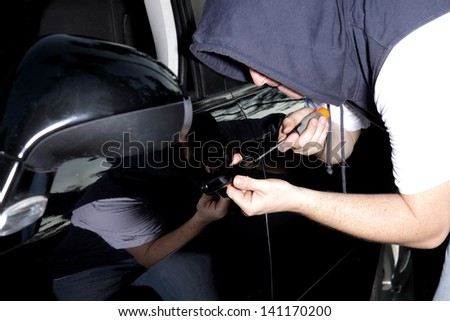 man in the night breaking into a car - stock photo