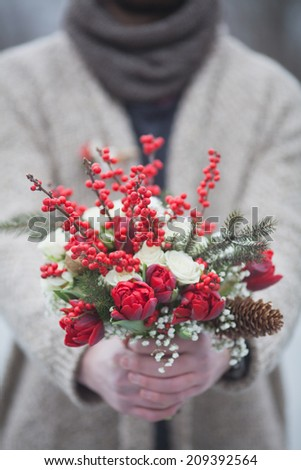 man in the park in winter with a bouquet of red flowers - stock photo