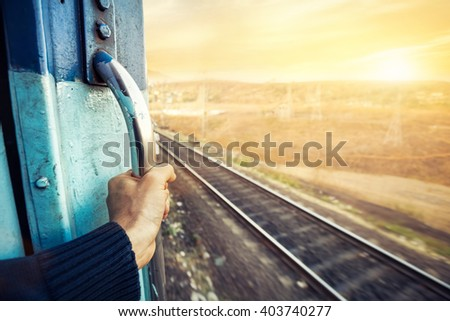 Man in the train passing desert area at sunset sky background in Rajasthan, India