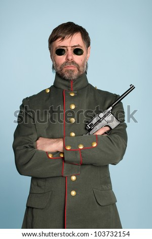 Man in the uniform of a military officer with a gun. - stock photo
