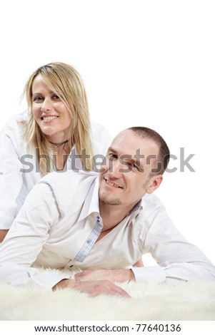 Man in the white shirt lies on the white shaggy carpet, woman sits near a little behind, their heads are turned a little aside. - stock photo