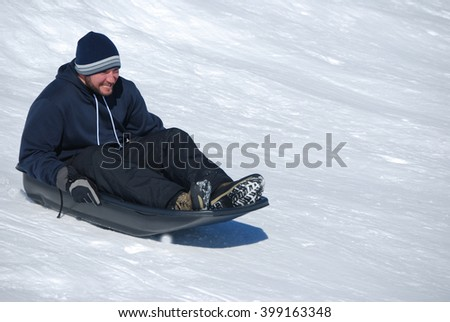 Man in toboggan on a sled on a snowhill going down laughing with copyspace. - stock photo