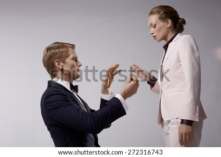 Man in toxedo, and woman in business suit in romantic relation