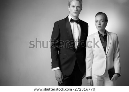 Man in toxedo, and woman in business suit in studio against wall - stock photo