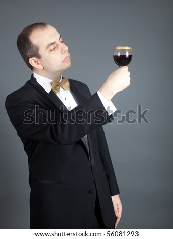 Man in tuxedo looking at the glass filled with red wine.