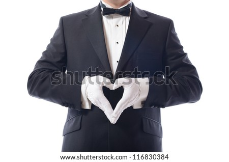 man in tuxedo with hands in heart shaped pose