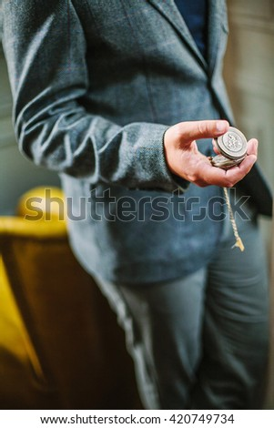 Man in tweed suit holding a vintage silver full hunter pocket watch in his hand, leaning to yellow armchair  - stock photo