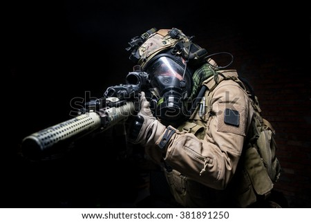 Man in uniform,helmet and gas mask aiming from assault rifle on  dark background/Soldier in gas mask aiming from his rifle.Selective focus - stock photo