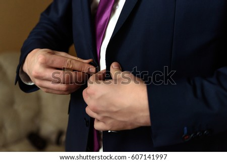 Man in violet tie buttons up blue jacket