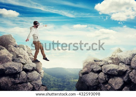 Man in virtual reality glasses is stepping carefully to walk on air between two high rocks on sunny valley