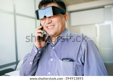 Man in virtual reality glasses talking on phone