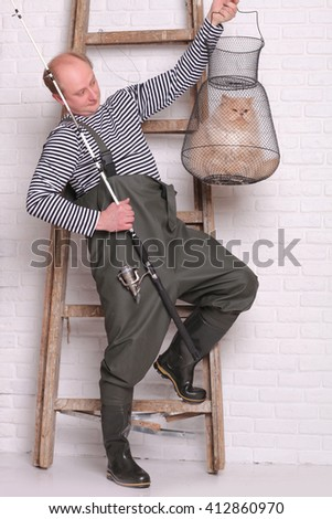 Man in waders stands near the ladder, holding a fishing equipment - stock photo