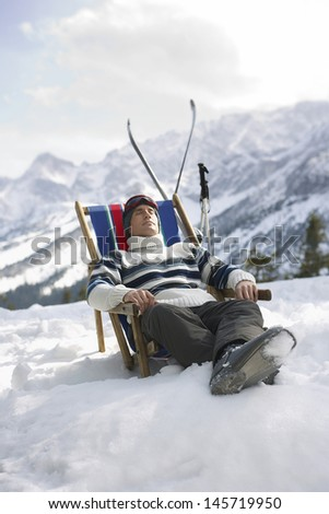 Man in warm clothing resting on deckchair in snowy mountains - stock photo
