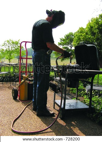 Man in welding helmet using a cutting torch to grill dinner