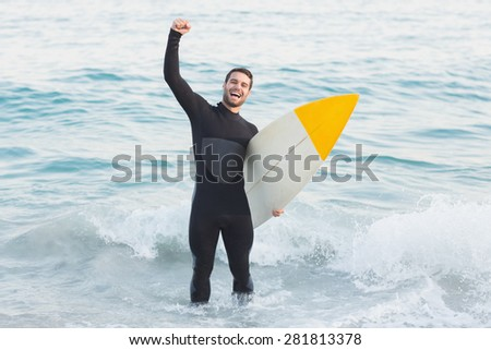 Man in wetsuit with a surfboard on a sunny day at the beach - stock photo