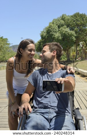 Man in wheelchair and girlfriend taking a selfie with smartphone - stock photo