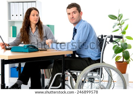 man in wheelchair and his  is female colleague working in the office - stock photo
