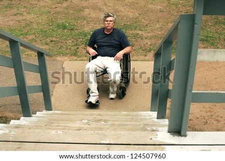 man in wheelchair facing a barrier of stairs - stock photo
