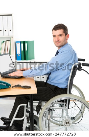 man in wheelchair is working in the office