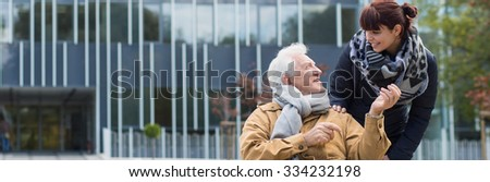 Man in wheelchair spending day outdoor with female friend - stock photo
