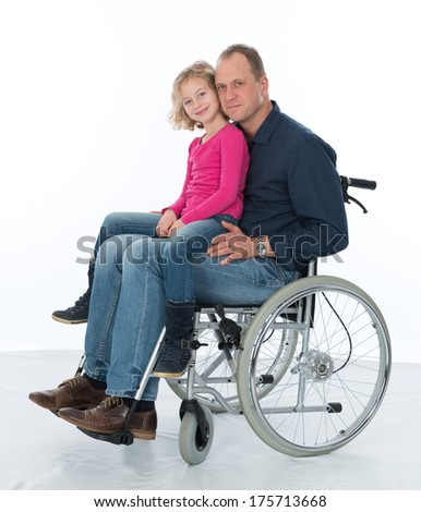 man in wheelchair with daughter - stock photo