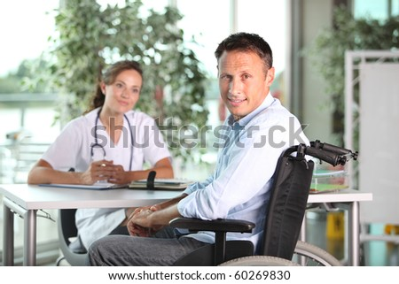 Man in wheelchair with doctor in hospital - stock photo