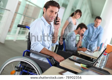 Man in wheelchair with mobile phone at work