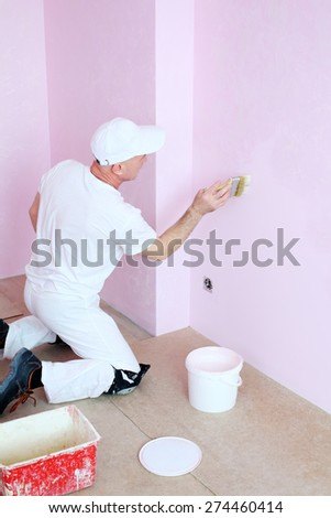 Man in white clothes covers the walls pink decorative plaster  - stock photo