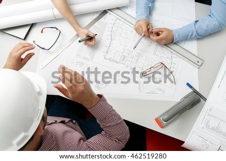 Man in white helmet sits at the table and analyzes the diagram