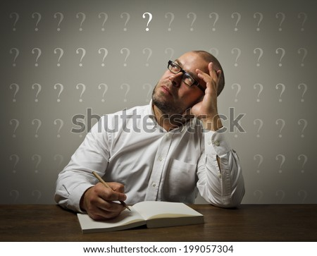 Man in white is sitting at the table and is ready to write something. Man in white is looking at the question mark. - stock photo