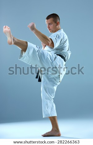 Man in white kimono and black belt training karate over blue background.