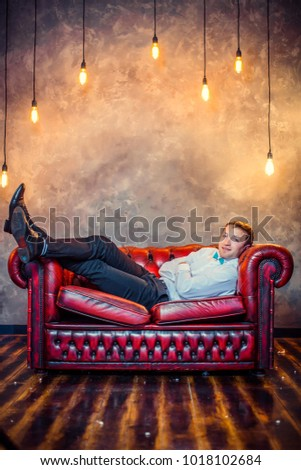 Man in white shirt and bow tie, lies in a leather red couch