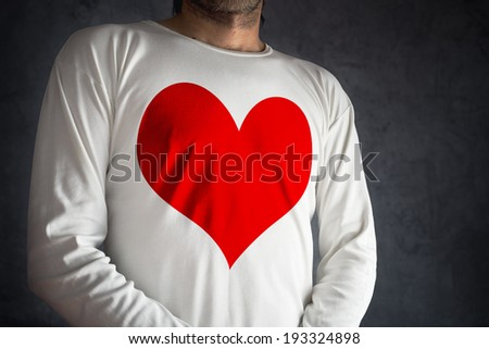 Man in white shirt with big red heart printed over his chest. Falling in love concept. - stock photo
