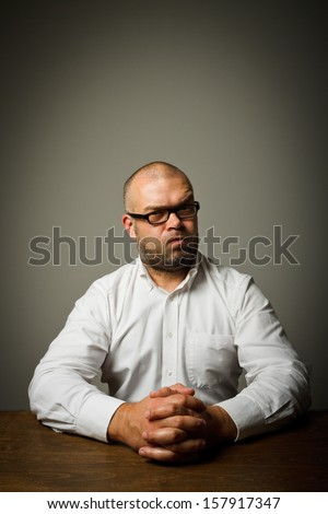 Man in white sitting at the table expressing his feelings and emotions.