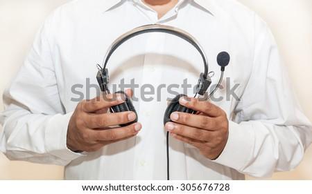 Man in white sleeve shirt holding headphone - stock photo