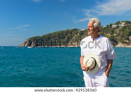 Man in white suit at the beach looking at the sea - stock photo