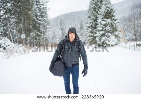 Man in white winter forest with backpack. Recreation and healthy lifestyle outdoors in snowy nature. Young male looking at camera and smiling. - stock photo