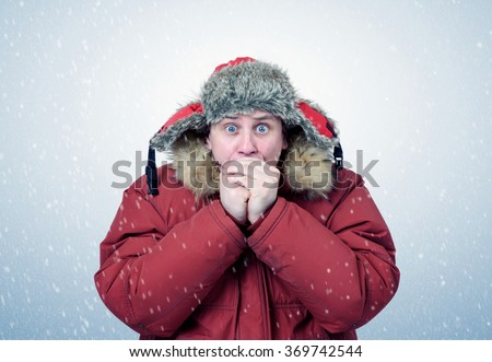 Man in winter clothes warming hands, cold, snow, blizzard - stock photo