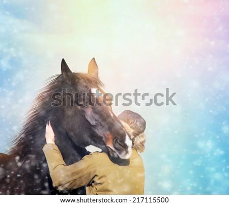 Man in winter hat hugging  horse in snowfall - stock photo