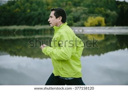 Man in yellow neon jacket runnig at the lake - stock photo