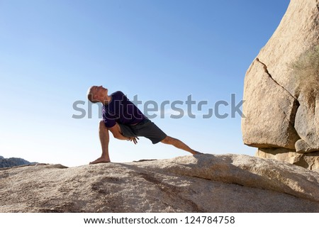 Man in yoga pose bound lunge outdoors in a spectatcular stone landscape. - stock photo