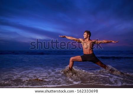 Man in yoga warrior pose on ocean beach at dusk - stock photo