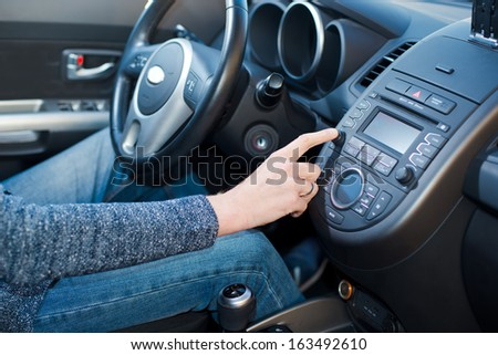 Man includes an audio system in the car. - stock photo