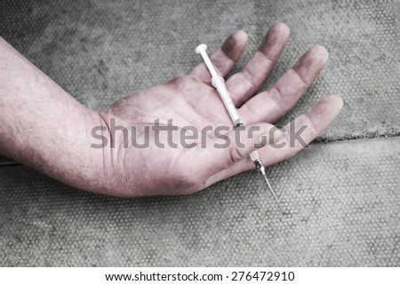 Man injecting himself with a small hypodermic needle possibly administering medication for a disease such as diabetes - stock photo