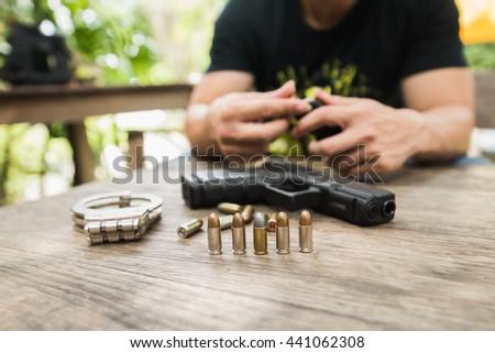 man input bullets gun wood table - stock photo