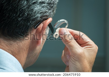 Man inserts hearing aid in his ear - stock photo